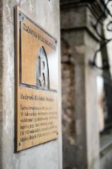 Tablica informacyjna na słupie bramy głównej